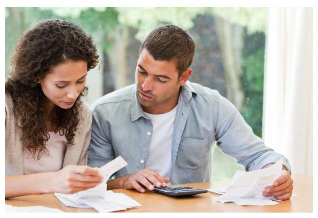 image of a couple looking at paperwork for blog post Money Management for Couples: Spending Discretion